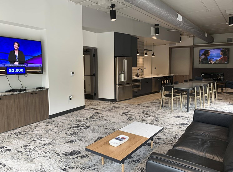 community room with lounge areas, TVs, and kitchen for entertaining
