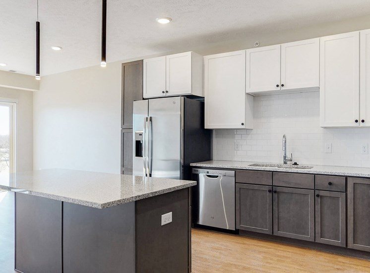 Beautiful kitchen completed with two tone slate finishes, including pendant lighting and stainless steel appliances in the Bliss floor plan at Haven at Uptown in Lincoln, NE
