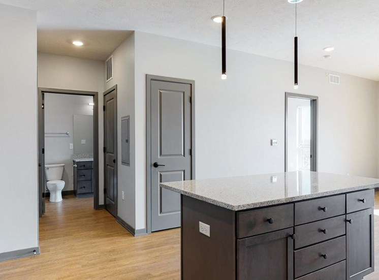 View of kitchen island and hallway leading to the bathroom in the Bliss floor plan at Haven at Uptown in Lincoln, NE