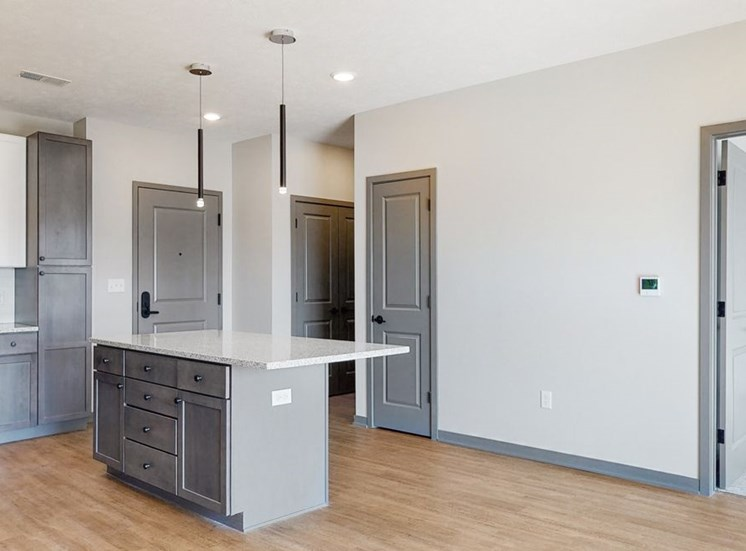 Pendant lighting and island providing seating in the Bliss floor plan kitchen at Haven at Uptown in Lincoln, NE