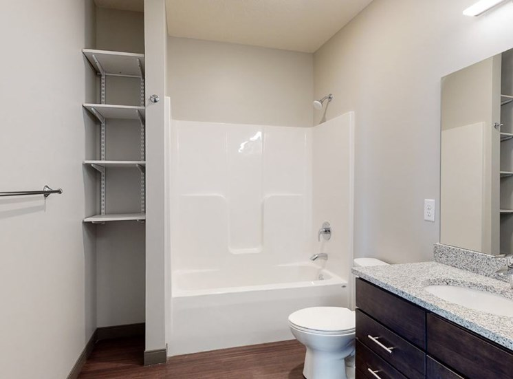 Bathroom with dual sink counter tops, a bathtub, and shelves for additional storage at Haven at Uptown in Lincoln, NE