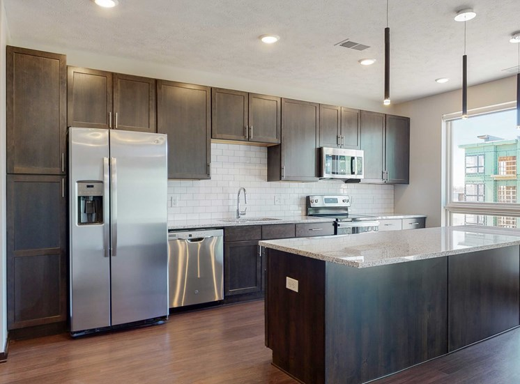 Spacious kitchen completed in the dual tone slate finish, including dark wood cabinets, dark wood style flooring, light granite counter tops, and white tile back splash in the Melody floor plan at Haven at Uptown in Lincoln, NE