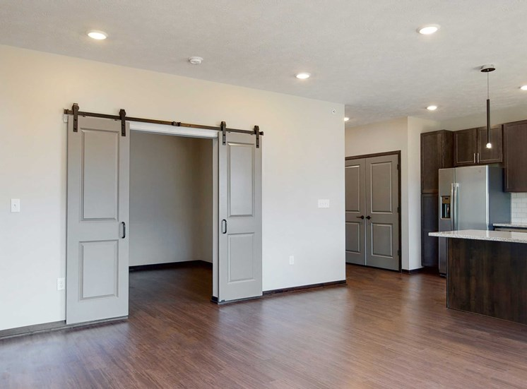 Living space with sliding barn doors leading to an office space in the Melody floor plan at Haven at Uptown in Lincoln, NE