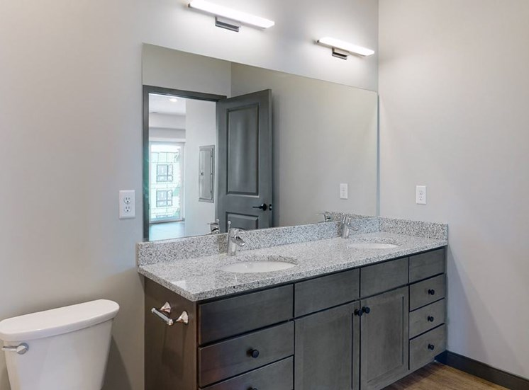 Dual sinks and light granite counter tops, as well is slate grey cabinetry for extra storage in the bathroom at Haven at Uptown in Linooln, NE