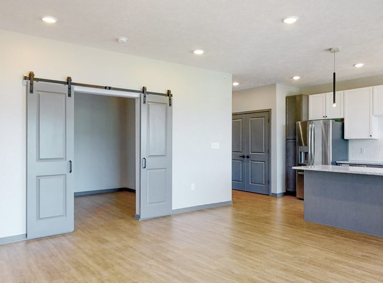 View of sliding barn doors leading into the office area from the living-dining space in the Melody floor plan at Haven at Uptown in Lincoln, NE