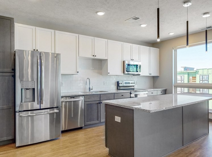 Large windows filter abundant natural light into the spacious kitchen in the Melody floor plan at Haven at Uptown in Lincoln, NE