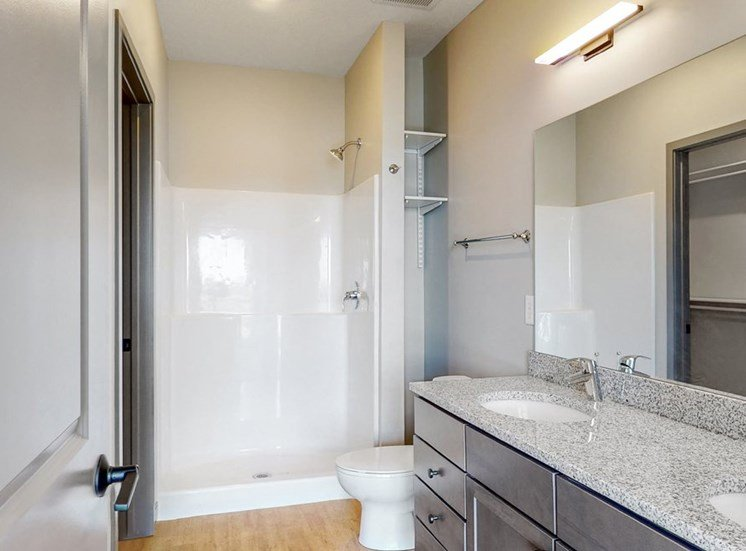 View of dual sink counter tops and shower in bathroom attached to the master bedroom at Haven at Uptown in Lincoln, NE