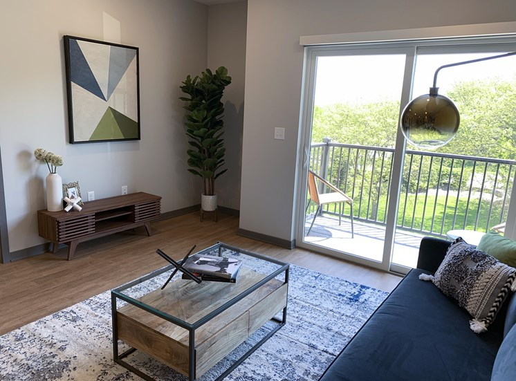 Spacious furnished living room with hard wood style flooring and scenic view of tree line in Lincoln at Haven at Uptown.
