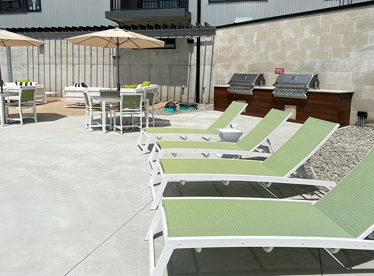 Row of light green lounge chairs and table with umbrellas near the pool at Haven at Uptown.