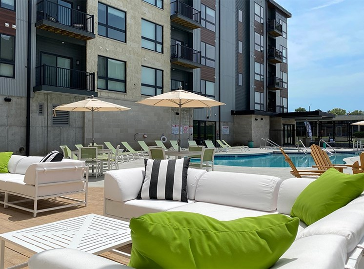 White outdoor sofa with decorative pillows near the pool outside Haven at Uptown.