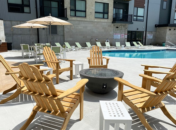 Wood Adirondack chairs arranged around a firepit near an outdoor pool at Haven at Uptown.