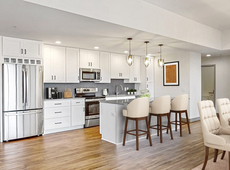 Create your culinary masterpiece in this chef's kitchen with seated island, stainless steel appliances, granite counter tops and custom tile backsplash in this 2 bedroom penthouse floor plan at Midtown Crossing Apartments Omaha.