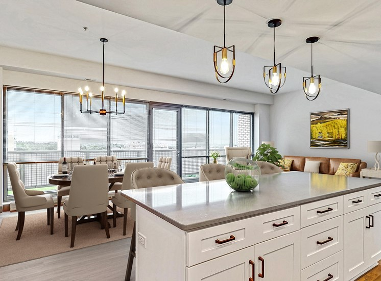 The fantastic chef's kitchen with seated island overlooks the spacious dining and living area 2 bedroom penthouse floor plan at Midtown Crossing Apartments Omaha.