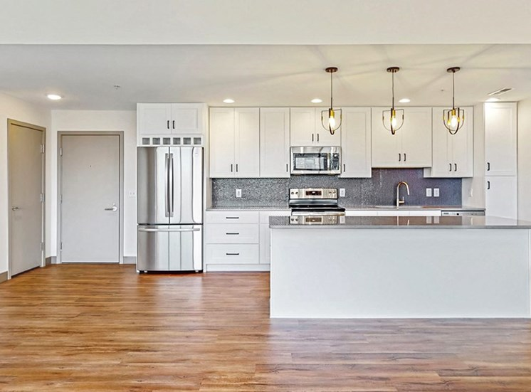 Create your culinary masterpiece in this chef's kitchen with seated island, stainless steel appliances, quartz counter tops and custom tile backsplash in this 2 bedroom penthouse floor plan at Midtown Crossing Apartments Omaha.