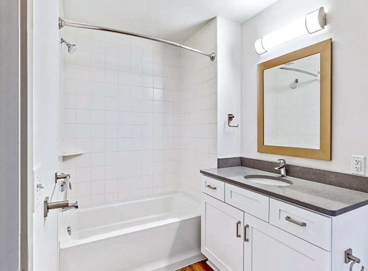 Spacious bathroom with tub and shower and large vanity in a 2 bedroom penthouse floor plan Midtown Crossing Apartments Omaha