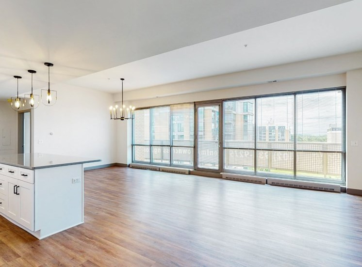Enjoy the scenic views from the floor-to-ceiling windows in the dining and living area of a 2 bedroom penthouse floor plan at Midtown Crossing Apartments Omaha