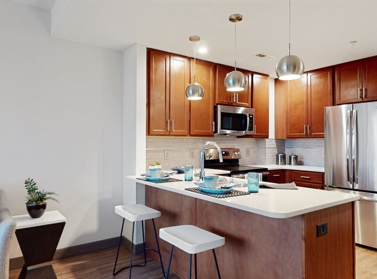 Kitchen with peninsula countertop, tile backsplash, and modern appliances in a 1 bedroom floor plan at Midtown Crossing Apartments Omaha