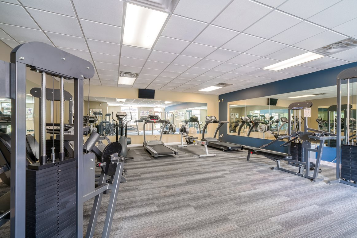 Bright and spacious exercise room featuring cardio machines, free weights, and weightlifting machines at Southwind Villas in LaVista NE 68128
