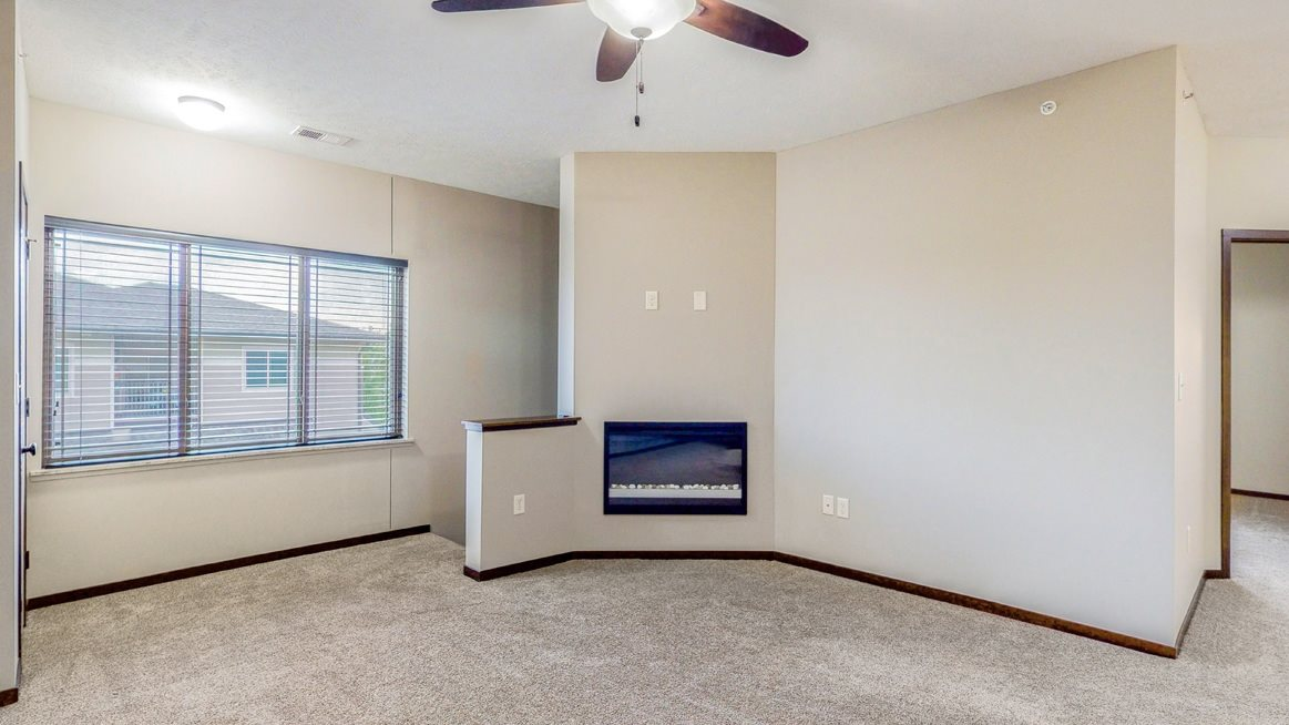 Living area with modern fireplace at The Villas at Wilderness Ridge luxury apartments in southwest Lincoln NE 68512