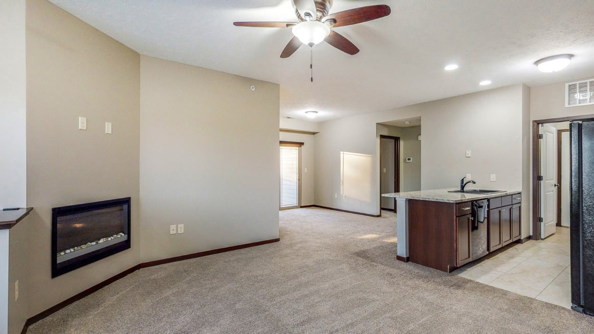 Living and dining area with modern fireplace at The Villas at Wilderness Ridge luxury apartments in southwest Lincoln NE 68512
