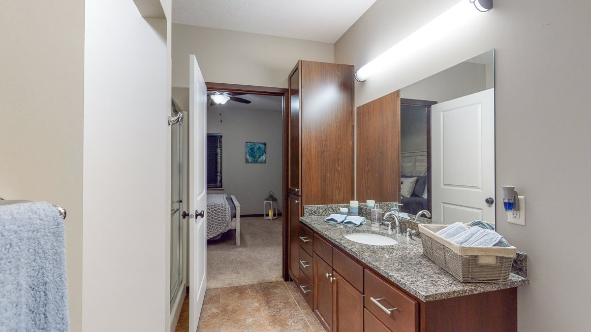The master bath in the Cedar floor plan features a large vanity, shower, and large linen cabinet.