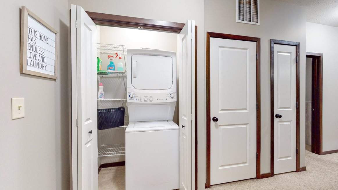 The Cedar features a full-size stacked washer and dryer.