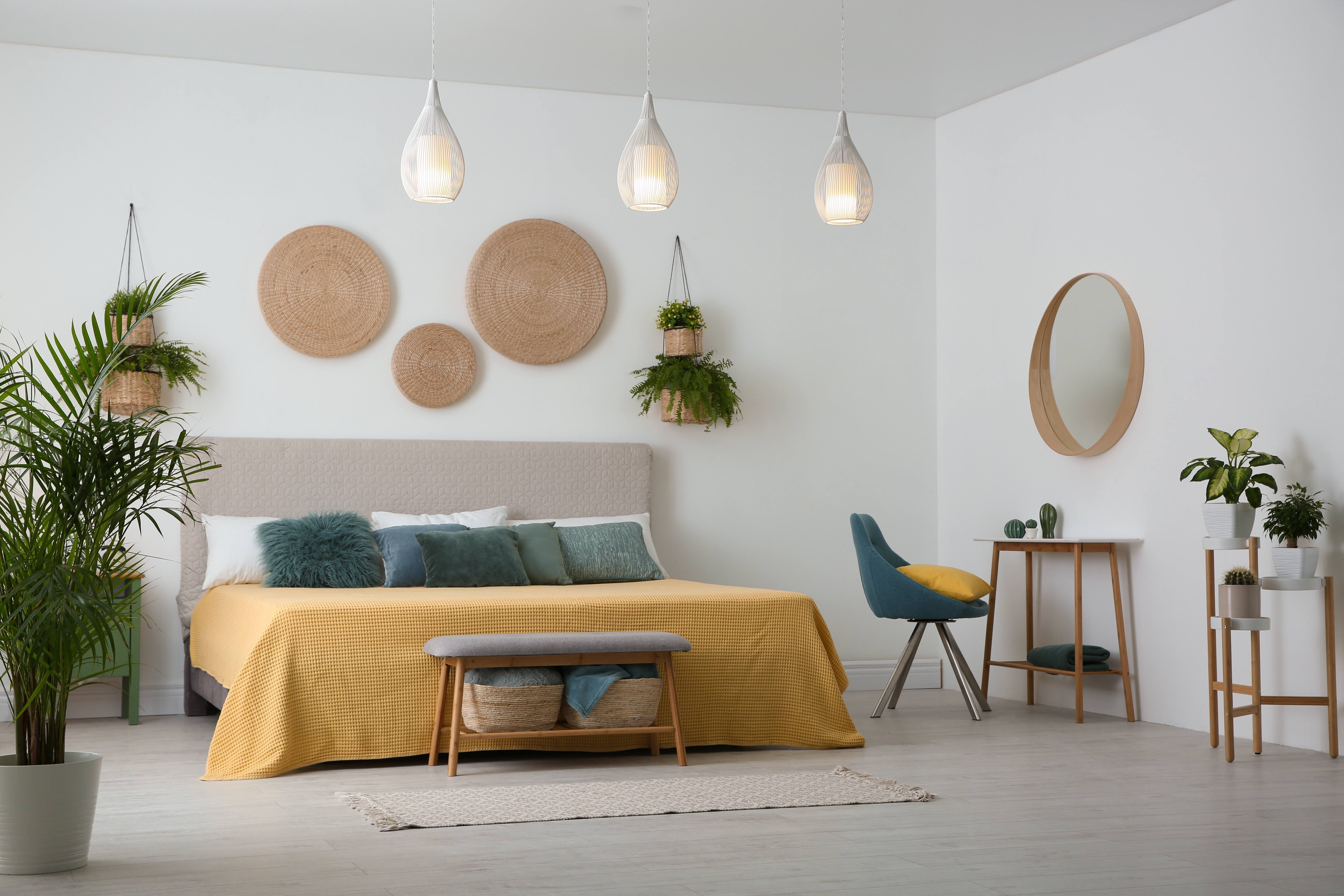 Bedroom with hanging lights, desk, plants and wall decor
