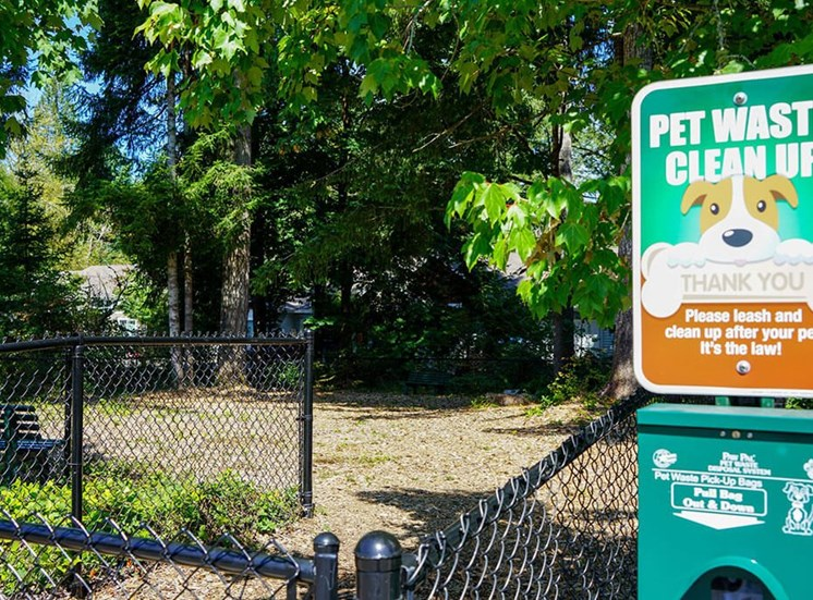 Pet-Friendly Apartments in Olympia, WA - Fenced Outdoor Pet Park With Bench and Surrounded by Trees
