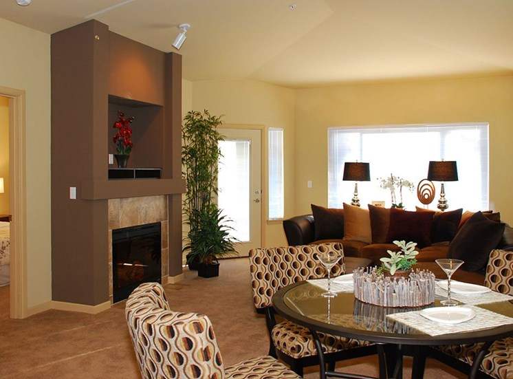 Olympia Apartments - Spacious Living Room With High Ceilings, Carpet, and Cozy Fireplace