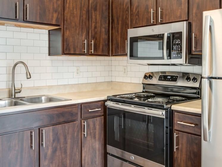 dark wood kitchen with stainless steel appliances