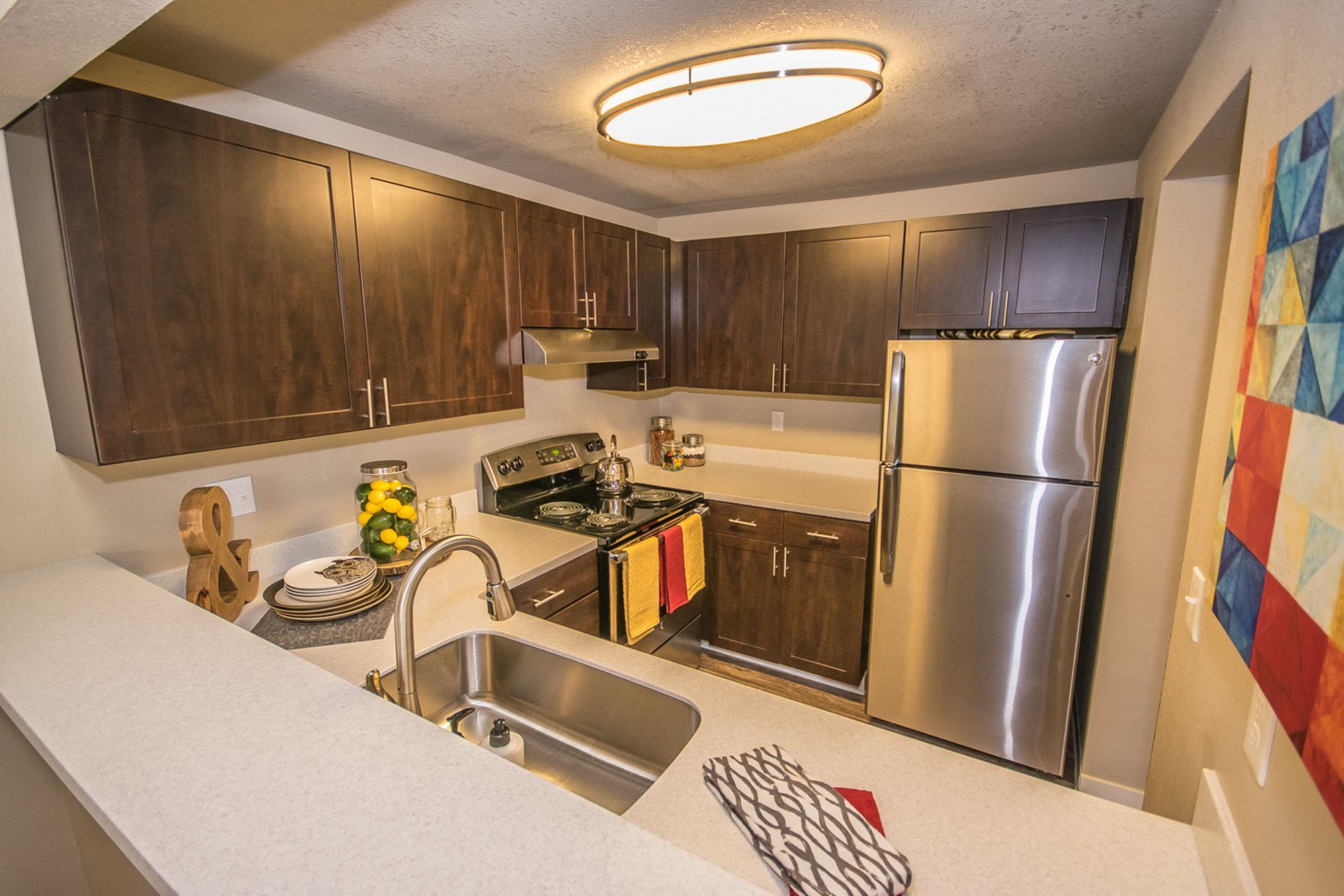 Apartments in Tacoma-The Fairways Apartments Kitchen with Matching Stainless-Steel Appliances, Lots of Storage Space, and Modern Lighting