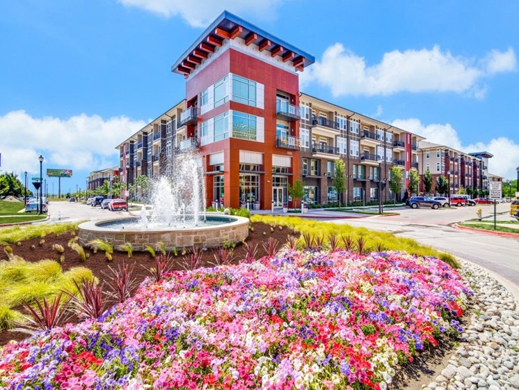 Rowlett Apartments – Harmony Luxury Apartments Exterior Building With a Beautiful Landscaping and Water Fountain