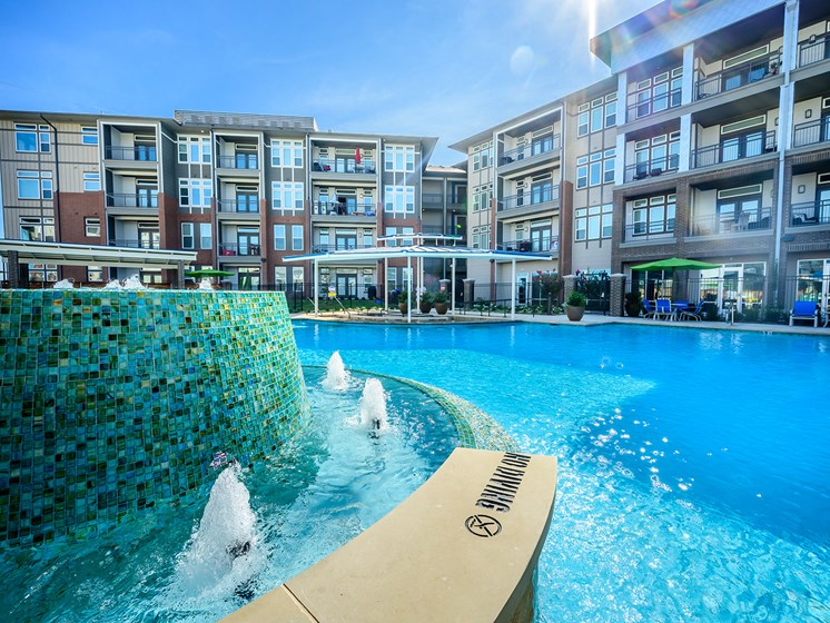 Rowlett Apartments for Rent - Harmony Luxury Apartments Exterior Pool with Spa and In-Water Lounge Chairs