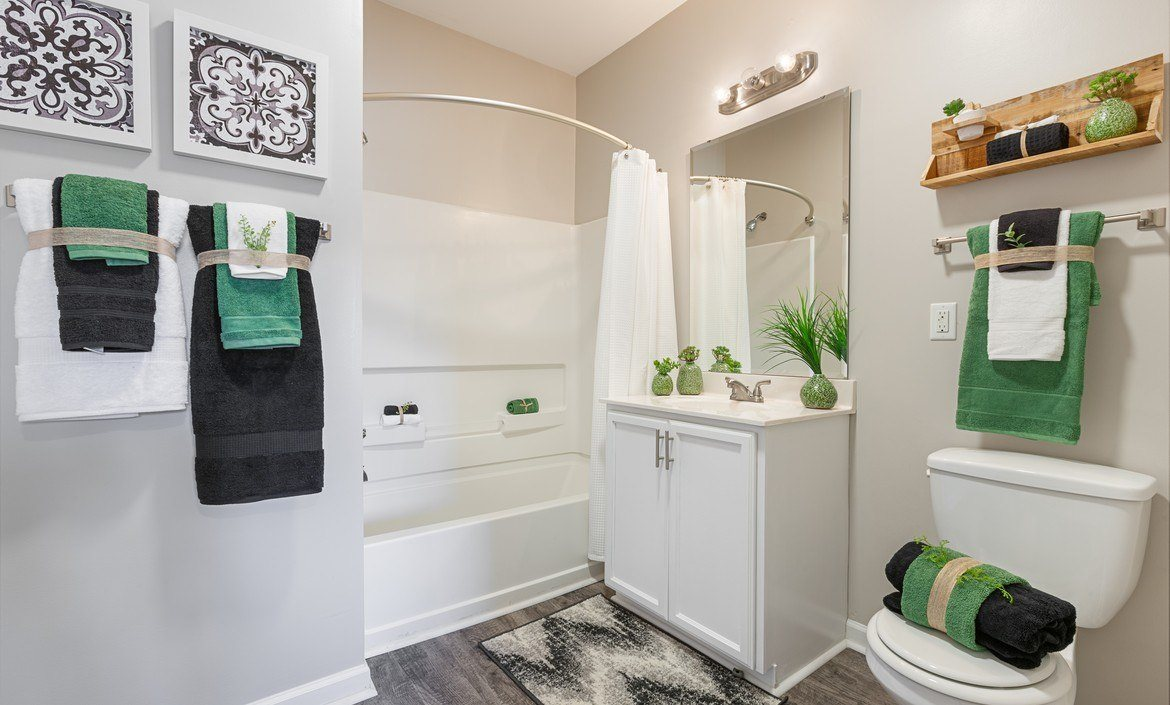 Spacious bathroom with vinyl flooring, a curved shower rod, white storage cabinets and soaking tub at The Summit on 401.