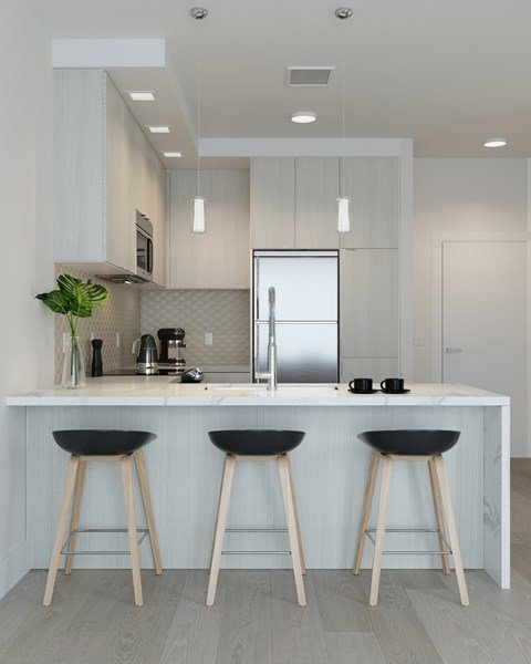 Kitchen with Light Finishes featuring Island with Waterfall Edge, Stainless Steel Whirlpool Appliances at Arrowwood Apartments in North Bethesda
