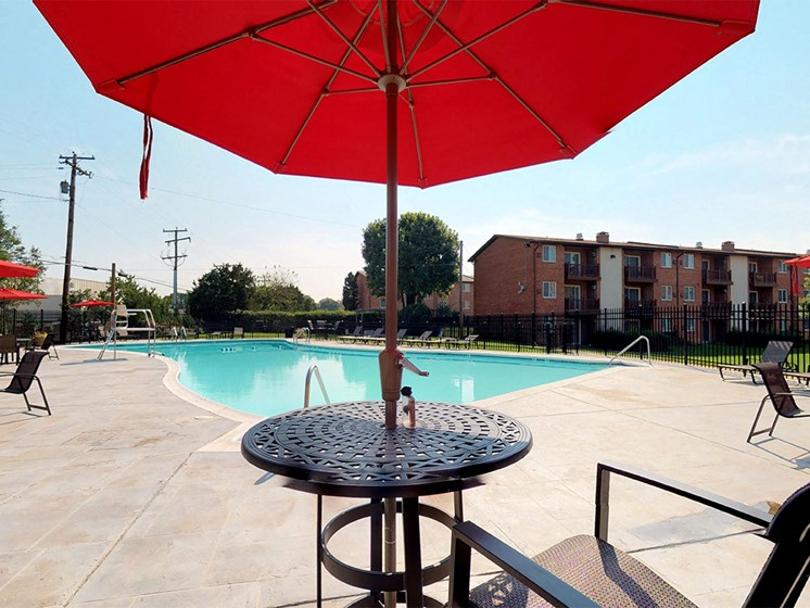 large red umbrella with table near side of the pool at Rose Hill Apartments, Alexandria, VA, 22310