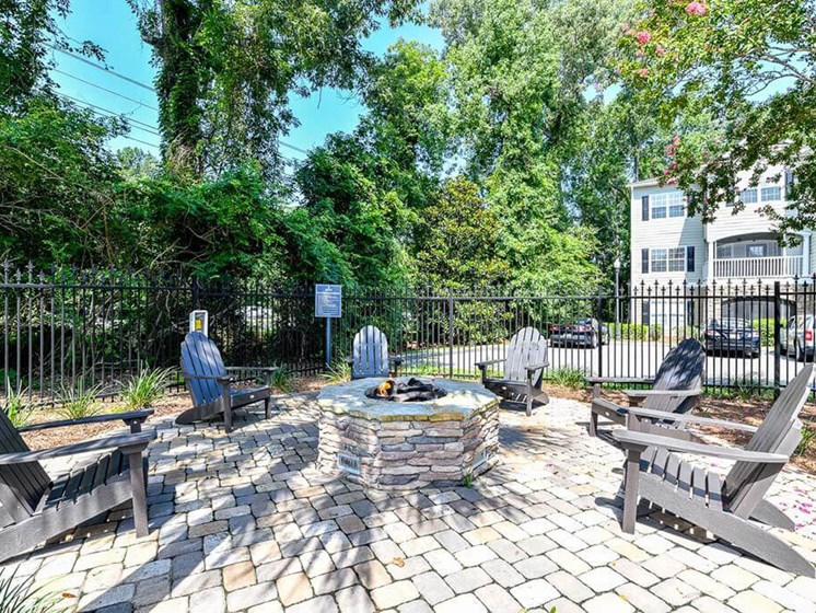Lounge chairs around fire pit by Relaxing Pool at Legends at Charleston Park Apartments, North Charleston, SC, 29420