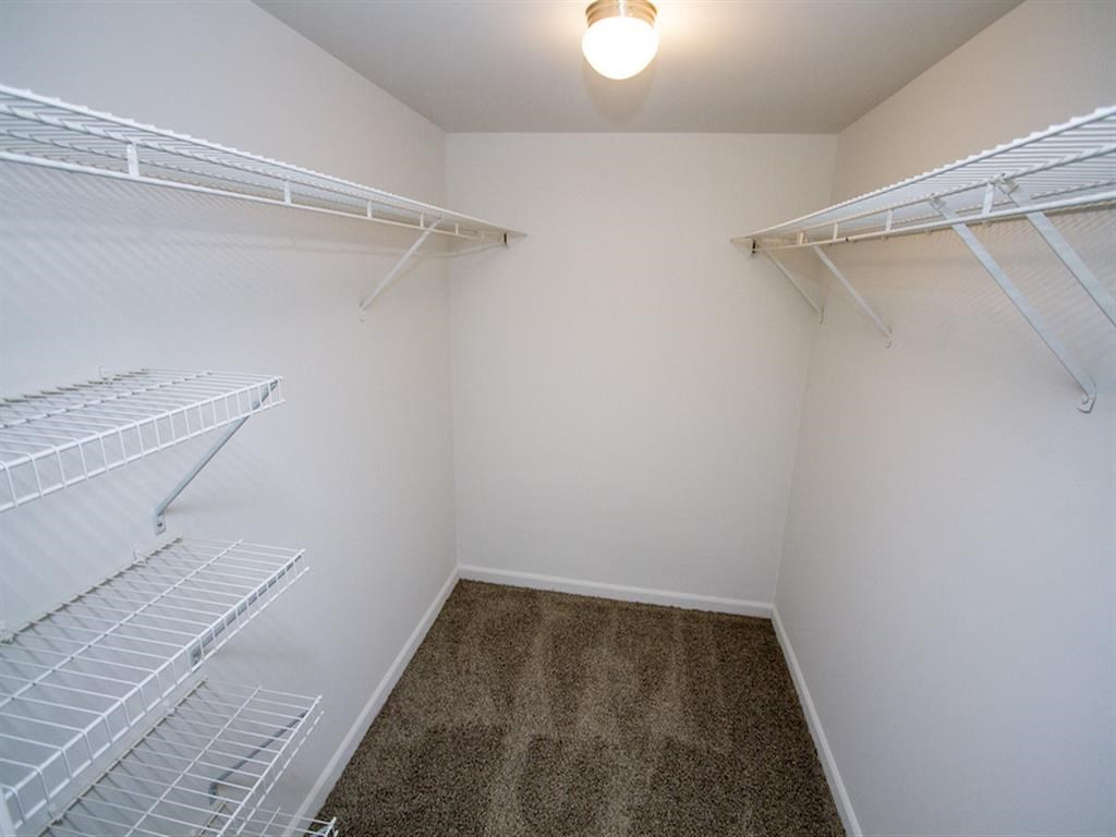 Walk-in closet with rack shelves and carpet floor-Quality Hill Square, Kansas City, MO