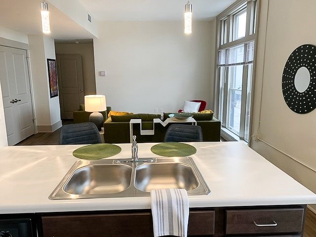 Apartment kitchen sink and countertop and living room furnished-The Arts Lofts at Dayton Arcade, Dayton, OH