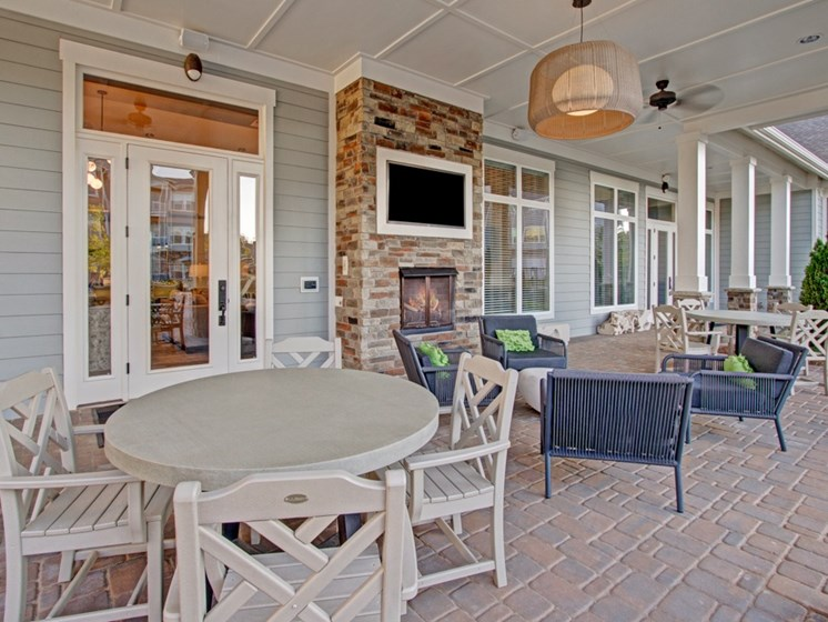 Outdoor Lounge & Entertainment. Chairs, fireplace, tv, windows, and door leading outside. at York Woods at Lake Murray Apartment Homes, South Carolina