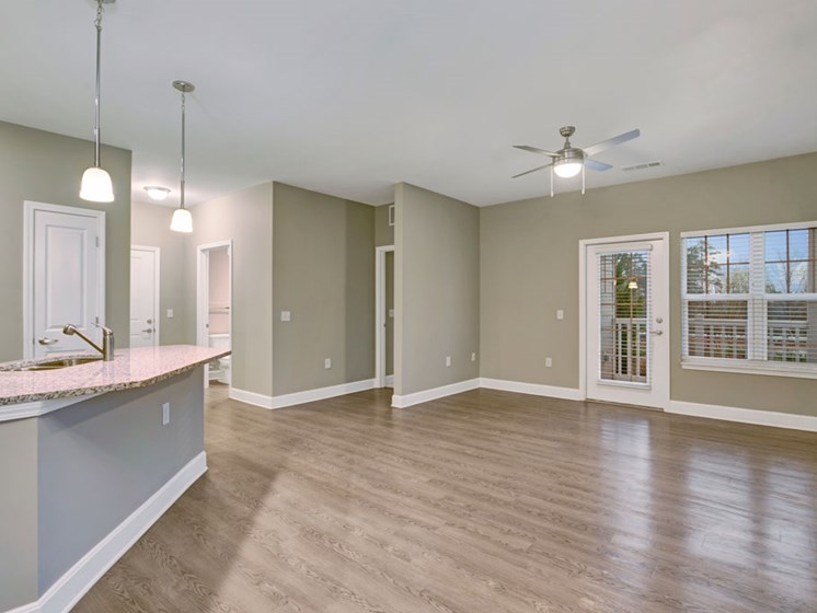 spacious living area with patio door and kitchen island at York Woods at Lake Murray Apartment Homes, Columbia, SC