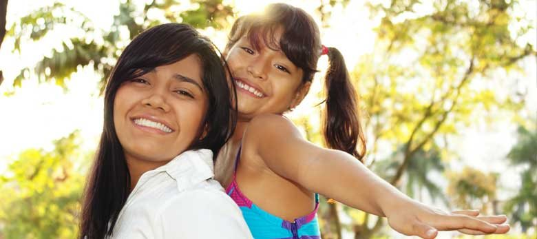 Happy mother and daughter in sunlit park