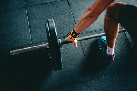 Man Exercising by Lifting Weights