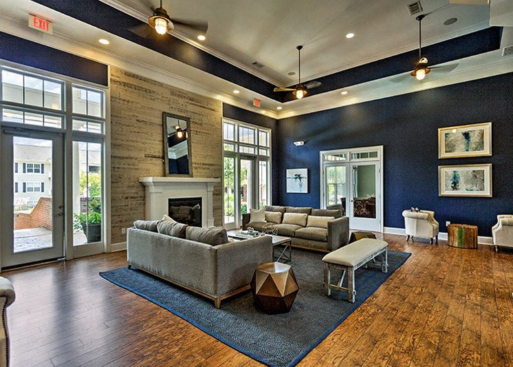 Spacious living room with lighted ceiling fan and crown molding at Abberly Green Apartment Homes by HHHunt, Mooresville North Carolina