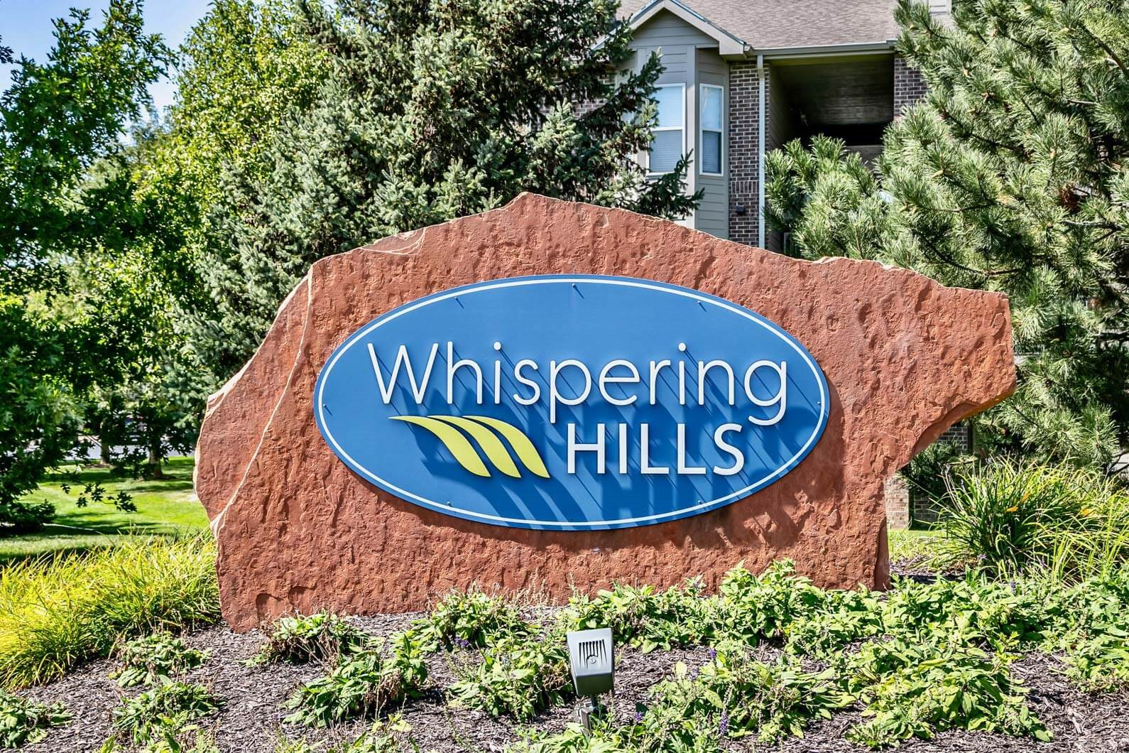 Property signage at Whispering Hills Apartments in Omaha, NE