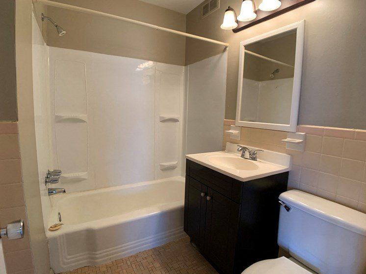 Bathroom with full-sized tub, vanity, and toilet
