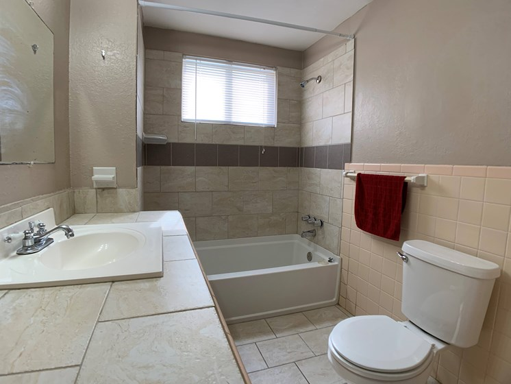 bathroom with large vanity, tub and toilet