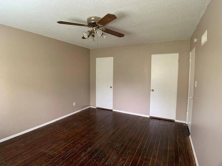 room with two closets and ceiling fan