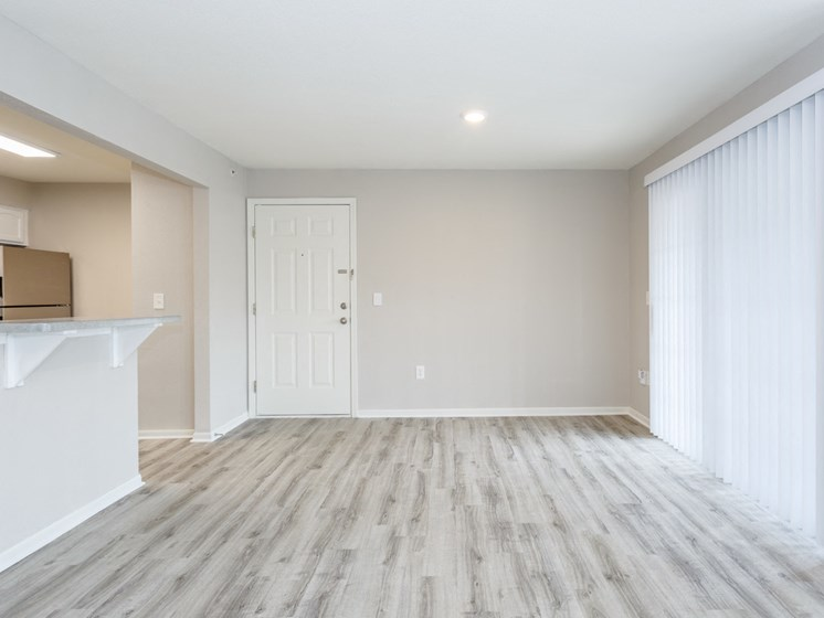 Living room with vinyl plank flooring with breakfast bar and patio