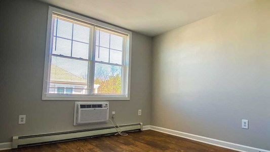 Large windows and AC wall unite in the bedroom.